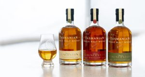 Image of three whisky bottles and a glass of whisky on a white bench